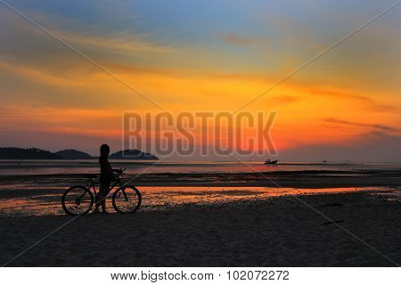 Silhouette Of Lonely Unidentified Girl With Bike On Beach With Sunset Light