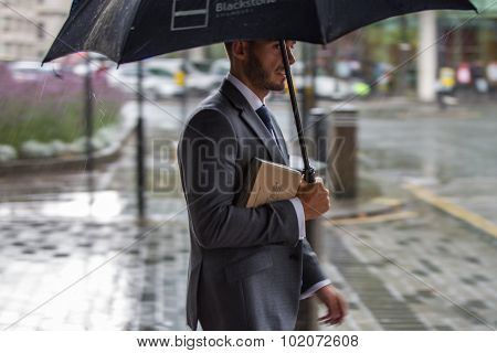 Businessman with umbrella  walking in rain. City of London