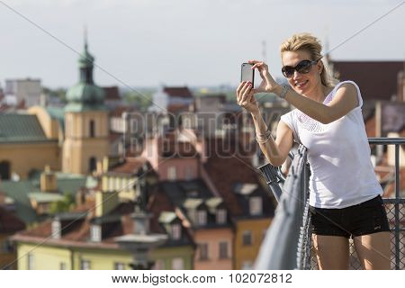 Cute young woman shoots on a smartphone Warsaw's old town.