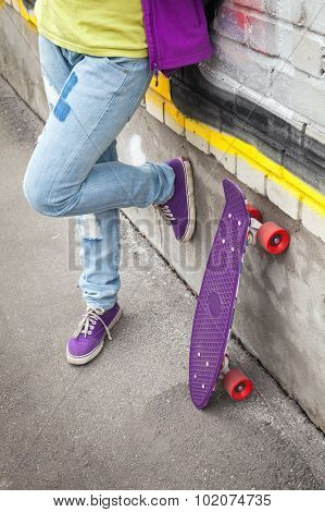 Teenager In Jeans Stands With Skateboard