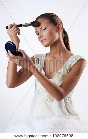 Young Woman Applying Cosmetics