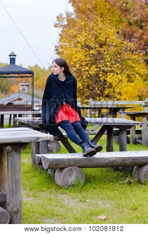 Pretty girl sitting on old wooden table in autumn park