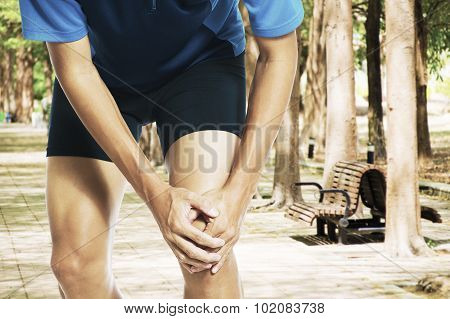 Male athlete runner touching foot in pain due to sprained ankle