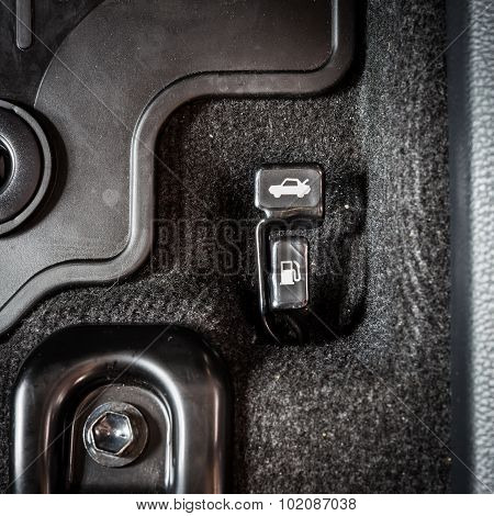 Close Up Hand Switch Of Car Fuel Tank And Hood. Car Interior