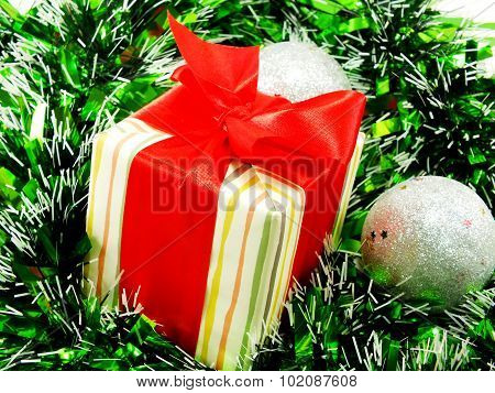Gift Box Present With Red Ribbon Decorations With Red And White Tinsel Christmas Background