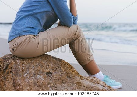 Beautiful Slim Woman Sitting On A Rock By The Sea