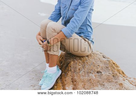 Beautiful Young Woman Sitting On A Rock By The Sea