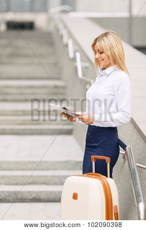 Positive woman standing near office building