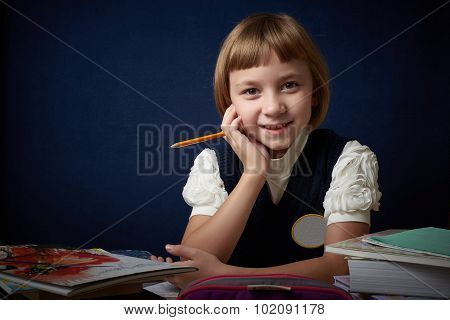Joyful schoolgirl sitting at her Desk.