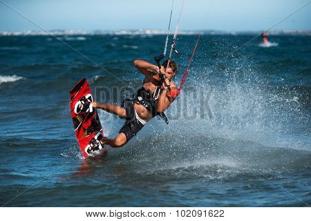 A kite surfer rides the waves.