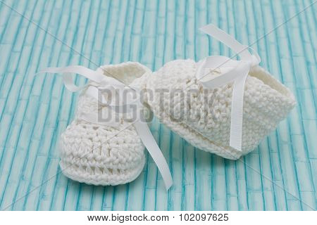 White Baby Booties On Wood Background