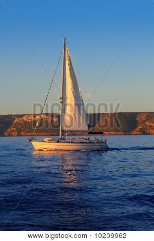 Regata de vela dourada nascer do sol no oceano azul