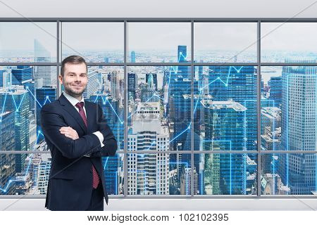 Smiling Handsome Businessman With Cross Hands Is Standing In The Modern Panoramic Office. Financial