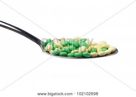 A Side View Of A Heap Of Yellow And Green Medicine Pills In A Spoon. Isolated On White Background.