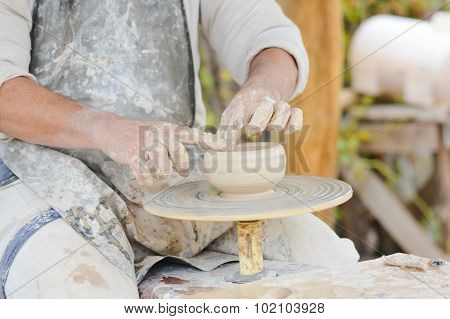 Potter hands forming clay and making little pot on wheel