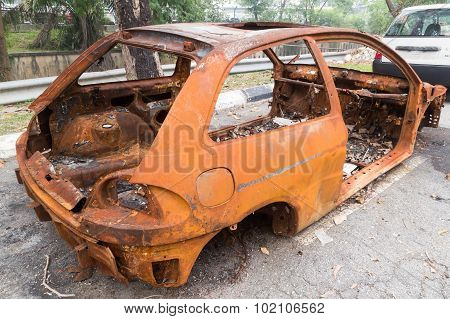 Rusty Chassis Of A Burnt Car Abandoned By The Side Of The Street.