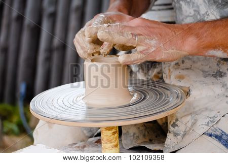 Closeup of potters hands working with clay on wheel carefully