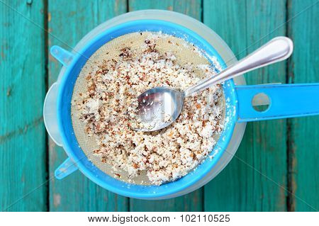 Almond Pulp On Blue Sieve With Spoon On Turquoise Wooden Table