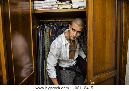Handsome shirtless young male lover hiding inside wardrobe