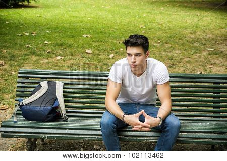 Young Male Student Sitting on Park Bench Seriously