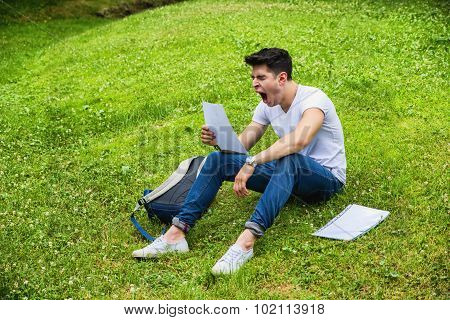 Young Bored, Tired Male Student Studying in City Park