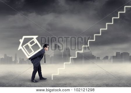 Male Investor Carrying House Icon Under Cloudy Day