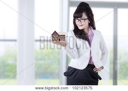 Woman Holding House Miniature