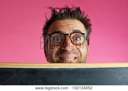 Nerd man crazy behind a blackboard and braces smile funny gesture in pink background