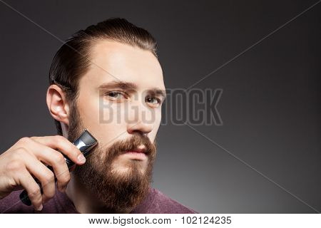 Attractive young bearded man is using shaver