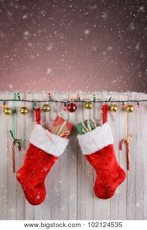 Christmas Stocking hanging on a rustic white fence with lights, jingle bells, and candy canes. Vertical format with snow effect.