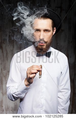 Handsome bearded hipster guy with cap and cigarette