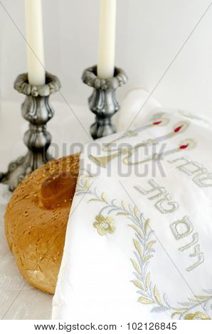 A concept photo of covered challah bread for the Jewish observance of Shabbat with candles in the background.