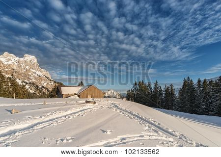 chalet with snow on austrian mountain at sunny winter day