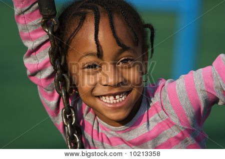 Young Girl Playing  On Swing  In Park