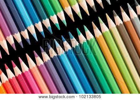 wooden color pencils lying in a row on black