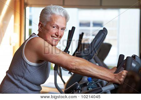 Senior Woman On Bike In Gym