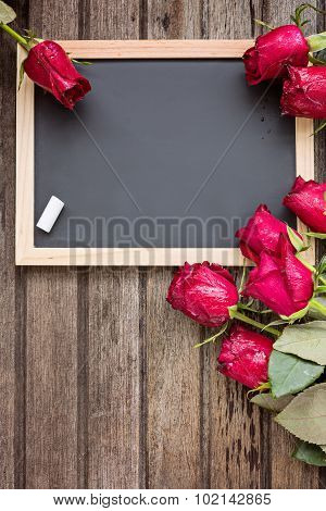 Black Board And Red Roses On Wooden Background, Top View, Vertical Composition