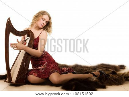 Blonde Woman With A Harp In Her Hand