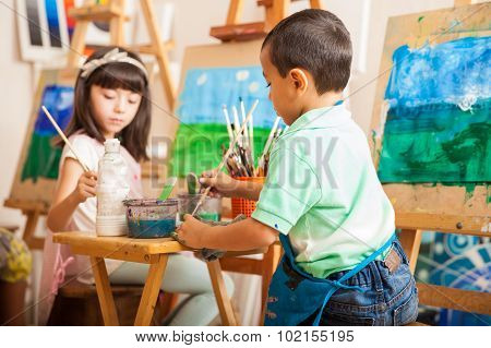 Little Kids Working On A Painting