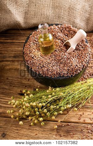 Mortar Bowl Full Of Flax Seeds With Spoon And Oil