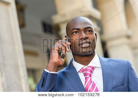 Black Businessman Talking With His Smart Phone In Urban Background