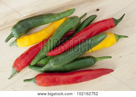 A heap of bright red, yellow and green chili peppers on a wooden board