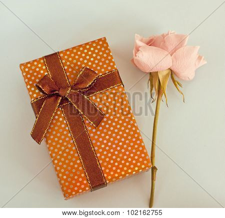 A photo of a gift box and a rose