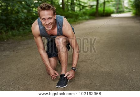 Smiling Fit Man Fixing His Shoelace At The Park