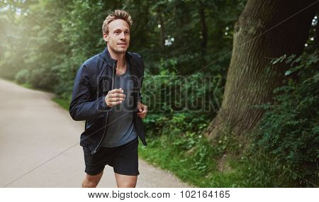 Healthy Man In Jacket Jogging At The Park