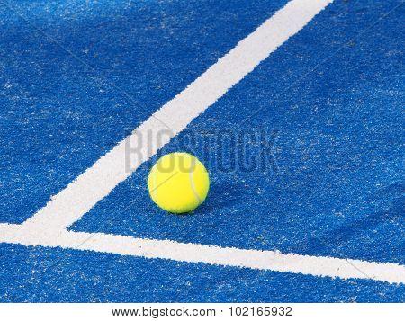 Single Tennis ball on a blue artificial grass court