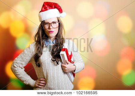 Young woman in Santa hat stressed on bright bokeh background