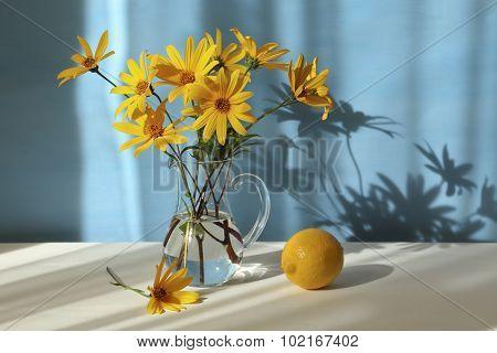 Jerusalem Artichoke Flowers And Lemon On Blue Background