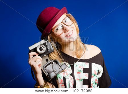 Pretty girl in hipster glasses and hat holding vintage camera