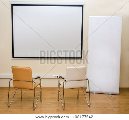 Blank White Screen And Roll-up Banner And Two Chairs